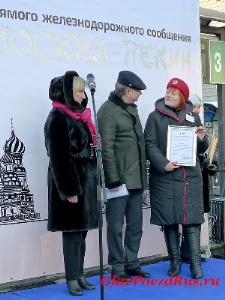 Владимир Каляпин и Лариса Дмитриева вручают почетную грамоту проводнику поезда №20/19 Кедрук Татьяне.