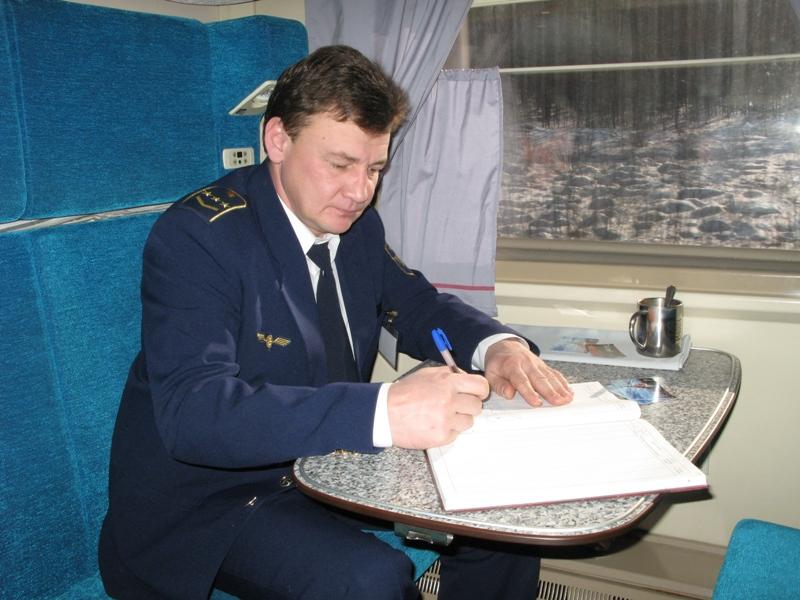 Начальник поезда «РОССИЯ» сообщением Москва-Владивосток Владимир Шмелев заполняет журнал опроса пассажиров.